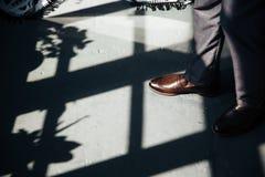 Τοπ άποψη ενός καλλιεργημένου πλαισίου σκιών στο πάτωμα από τα μεγάλα stained-glass παράθυρα, ακριβά μοντέρνα κλασικά παπούτσια α Στοκ φωτογραφία με δικαίωμα ελεύθερης χρήσης