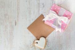 Τοπ άποψη ενός κιβωτίου δώρων που τυλίγεται στο ρόδινο διαστιγμένο έγγραφο, διαμορφωμένο καρδιά μπισκότο αγάπης και μια κενή κάρτ Στοκ Εικόνες