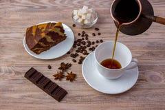 Τοπ άποψη ενός κύπελλου με τους κύβους ζάχαρης, τα φασόλια καφέ, ένα κομμάτι του καταπληκτικού κέικ σε ένα πιατάκι και ένα BA φλι Στοκ Εικόνες