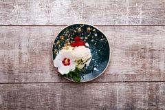 Τοπ άποψη ενός παγωτού βανίλιας σε ένα πιάτο Παγωτό με τα μούρα, μέντα, καρύδια Γλυκό επιδόρπιο σε ένα ξύλινο υπόβαθρο διάστημα α στοκ φωτογραφίες
