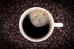 Τοπ άποψη ενός φλιτζανιού του καφέ στα φασόλια καφέ Στοκ φωτογραφίες με δικαίωμα ελεύθερης χρήσης