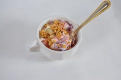 Τοπ άποψη ενός φλυτζανιού του γιαουρτιού με το κάλυμμα granola με το κουτάλι Στοκ Φωτογραφίες
