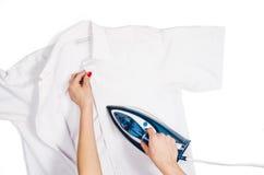 Τοπ άποψη ενδυμάτων σιδερώματος χεριών γυναικών σχετικά με το άσπρο υπόβαθρο Στοκ φωτογραφία με δικαίωμα ελεύθερης χρήσης