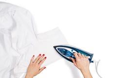 Τοπ άποψη ενδυμάτων σιδερώματος χεριών γυναικών σχετικά με το άσπρο υπόβαθρο Στοκ Εικόνες