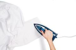Τοπ άποψη ενδυμάτων σιδερώματος χεριών γυναικών σχετικά με το άσπρο υπόβαθρο Στοκ φωτογραφίες με δικαίωμα ελεύθερης χρήσης