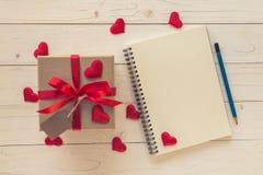 Τοπ άποψη επάνω από το κιβώτιο δώρων και την κόκκινη κόκκινης καρδιά κορδελλών και με τη σημείωση Στοκ Εικόνες