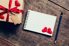 Τοπ άποψη επάνω από το κιβώτιο δώρων και την κόκκινη κόκκινης καρδιά κορδελλών και με τη σημείωση Στοκ Φωτογραφίες
