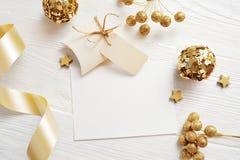 Τοπ άποψη ευχετήριων καρτών Χριστουγέννων προτύπων και χρυσή σφαίρα, flatlay σε ένα άσπρο ξύλινο υπόβαθρο με μια κορδέλλα, με τη  στοκ εικόνες