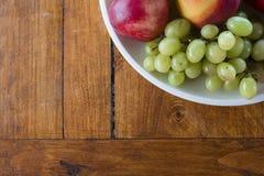 Τοπ άποψη κύπελλων φρούτων σχετικά με το ξύλινο επιτραπέζιο υπόβαθρο στοκ φωτογραφίες