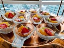 Τοπ άποψη μίνι tarts με τις φρέσκα φράουλες, το πορτοκάλι και το ακτινίδιο στο κουτάλι στοκ φωτογραφίες