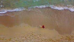 Τοπ άποψη μιας γυναίκας που περπατά χωρίς παπούτσια κατά μήκος της υγρής παραλίας άμμου Το τρέχοντας κύμα πλένει μακριά τα ίχνη σ απόθεμα βίντεο
