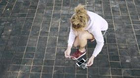 Τοπ άποψη μιας γυναίκας jogger που δένει το κορδόνι της και που αρχίζει να τρέχει έξω φιλμ μικρού μήκους
