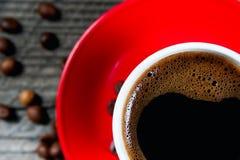 Τοπ άποψη μια κόκκινη κούπα της σκοτεινής κινηματογράφησης σε πρώτο πλάνο καφέ Στοκ Εικόνα