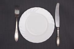 Τοπ άποψη πιάτων, δικράνων και μαχαιριών σχετικά με το μαύρο υπόβαθρο υφασμάτων Στοκ Εικόνα
