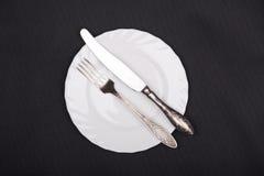 Τοπ άποψη πιάτων, δικράνων και μαχαιριών σχετικά με το μαύρο υπόβαθρο υφασμάτων Στοκ Φωτογραφία