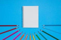Τοπ άποψη σχετικά με ένα βιβλίο σημειώσεων με τα μολύβια κενών και χρώματος σε ένα μπλε υπόβαθρο Στοκ φωτογραφίες με δικαίωμα ελεύθερης χρήσης
