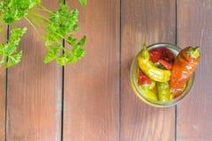 Τοπ άποψη σχετικά με τα ανοικτά παστωμένα πιπέρια τσίλι στο βάζο γυαλιού με Parsle Στοκ Εικόνες