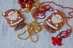 Τοπ άποψη σχετικά με τα εορταστικά μπισκότα μελιού στη μορφή Santa με τις διαφορετικές διακοσμήσεις Χριστουγέννων Στοκ Φωτογραφίες