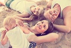 Τοπ άποψη σχετικά με τους γονείς με τα παιδιά που χαλαρώνουν στην παραλία στοκ εικόνες