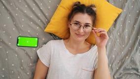 Τοπ άποψη σχετικά με το νέο γοητευτικό κορίτσι στα γυαλιά που βρίσκονται στο κρεβάτι, που χαμογελούν χαρωπά στη κάμερα και που με απόθεμα βίντεο
