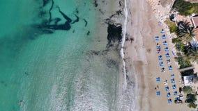 Τοπ άποψη της αμμώδους παραλίας στις ακτές του κρυστάλλου - σαφής θάλασσα με τους αργοσχόλους και τους φιλοξενουμένους ήλιων φιλμ μικρού μήκους