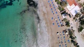Τοπ άποψη της αμμώδους παραλίας στις ακτές του κρυστάλλου - σαφής θάλασσα που εξοπλίζεται με τους αργοσχόλους ήλιων, κόλπος κοραλ απόθεμα βίντεο