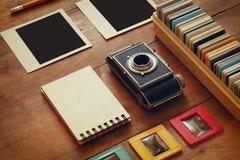 Τοπ άποψη της εκλεκτής ποιότητας κάμερας και των παλαιών πλαισίων φωτογραφικών διαφανειών πέρα από το ξύλινο επιτραπέζιο υπόβαθρο Στοκ Φωτογραφία