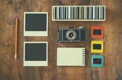 Τοπ άποψη της εκλεκτής ποιότητας κάμερας και των παλαιών πλαισίων φωτογραφικών διαφανειών πέρα από το ξύλινο επιτραπέζιο υπόβαθρο Στοκ φωτογραφία με δικαίωμα ελεύθερης χρήσης