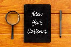 Τοπ άποψη της ενίσχυσης - γυαλί, τη μάνδρα και το σημειωματάριο που γράφονται με Know τον πελάτη σας στο ξύλινο υπόβαθρο Έννοια ε απεικόνιση αποθεμάτων