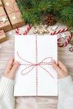 Τοπ άποψη της επιστολής Χριστουγέννων υπό εξέταση Κλείστε επάνω των χεριών κρατώντας το κενό wishlist στον ξύλινο πίνακα με τη δι Στοκ Φωτογραφία