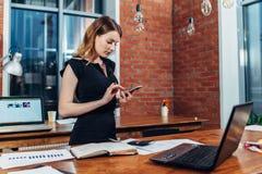 Τοπ άποψη της εργασίας γυναικών χρησιμοποιώντας το smartphone που στέκεται στον εργασιακό χώρο της στο δημιουργικό γραφείο στοκ εικόνες