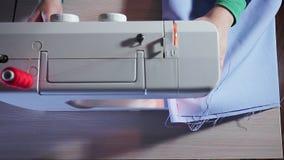 Τοπ άποψη της ράβοντας μηχανής Seamstress είναι εργασία, κάνοντας μια ραφή στο ύφασμα φιλμ μικρού μήκους