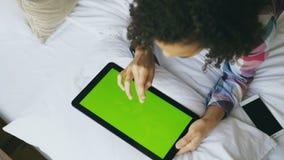 Τοπ άποψη της σγουρής μικτής γυναίκας φυλών που βρίσκεται στο κρεβάτι που χρησιμοποιεί στο σπίτι την ηλεκτρονική ταμπλέτα με την  φιλμ μικρού μήκους