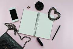 Τοπ άποψη της τσάντας μαύρων γυναικών με το κενά σημειωματάριο, τη μάνδρα, τα καλλυντικά, τα εξαρτήματα και Iphone5 στο ρόδινο υπ Στοκ φωτογραφίες με δικαίωμα ελεύθερης χρήσης