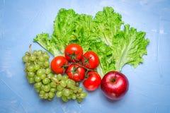 Τοπ άποψη της υγιεινής διατροφής: ντομάτα, μήλο, σταφύλι, σαλάτα Υγιές ea Στοκ Εικόνες