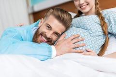 Τοπ άποψη της χαμογελώντας εγκύου γυναίκας με το σύζυγο που αγκαλιάζει την κοιλιά Στοκ Φωτογραφίες