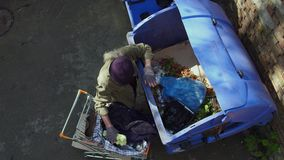Τοπ άποψη του άστεγου πλησιάζοντας δοχείου απορριμμάτων ατόμων με το κάρρο αγορών φιλμ μικρού μήκους