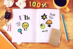 Τοπ άποψη του ανοικτού βιβλίου σημειώσεων με τα επιχειρησιακά σκίτσα, το φλιτζάνι του καφέ και το τσαλακωμένο έγγραφο Στοκ Εικόνες