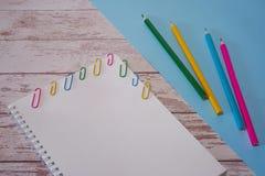 Τοπ άποψη του ανοικτού sketchbook με την κενή σελίδα copyspace και των ζωηρόχρωμων χαρτικών σε ένα ξύλινο γραφείο και ένα μπλε υπ στοκ φωτογραφίες με δικαίωμα ελεύθερης χρήσης