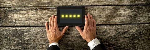 Τοπ άποψη του αρσενικού χεριού που κρατά την ψηφιακή ταμπλέτα με πέντε χρυσό ST στοκ φωτογραφία με δικαίωμα ελεύθερης χρήσης