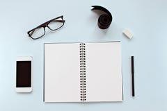Τοπ άποψη του γραφείου χώρου εργασίας με το κενό σημειωματάριο, τα γυαλιά ματιών, τα έξυπνα χαρτικά τηλεφώνων, κορδελλών και γραφ Στοκ Φωτογραφίες