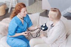 Τοπ άποψη του εύθυμου caregiver που ελέγχει την πίεση της ανώτερης γυναίκας Στοκ Εικόνες