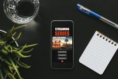 Τοπ άποψη του ιστοχώρου app τηλεοπτικής σειράς σε μια τηλεφωνική οθόνη, που τοποθετείται σε ένα μαύρο γραφείο Στοκ Εικόνες