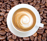 Τοπ άποψη του καυτού cappuccino καφέ που απομονώνεται στα φασόλια καφέ backg Στοκ Εικόνες