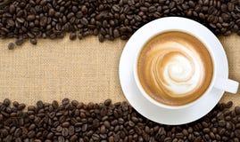 Τοπ άποψη του καυτού cappuccino με τα φασόλια καφέ burlap backgroun Στοκ φωτογραφίες με δικαίωμα ελεύθερης χρήσης