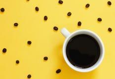 Τοπ άποψη του καφέ και των φασολιών καφέ στο κίτρινο υπόβαθρο στοκ φωτογραφίες