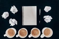 Τοπ άποψη του κενού σημειωματάριου με τα ακατάστατα τσαλακωμένα έγγραφα και τα φλιτζάνια του καφέ στη σειρά Στοκ φωτογραφία με δικαίωμα ελεύθερης χρήσης