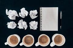 Τοπ άποψη του κενού σημειωματάριου με τα τσαλακωμένα έγγραφα και τα φλιτζάνια του καφέ στη σειρά Στοκ Εικόνα