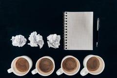 Τοπ άποψη του κενού σημειωματάριου με τα τσαλακωμένα έγγραφα και τα φλιτζάνια του καφέ στη σειρά Στοκ Εικόνες