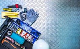 Τοπ άποψη του κιβωτίου και του κράνους εργαλείων στο ελεγμένο υπόβαθρο πιάτων στο εργαστήριο Σύνολο εργαλείων υπηρεσιών Εγχώριο κ στοκ φωτογραφία